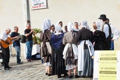 Amatörer i traditionella klänningar som dansar folkdans Arkivfoto
