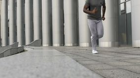 Amatörmässig jogger som utarbetar bredvid enorm kontorsbyggnad som utbildar i centrum stock video