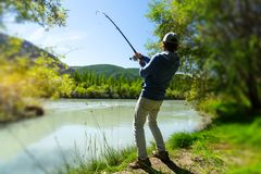 Amateur angler fishing. In the rapid river in mountains. Altai, Russia royalty free stock photos