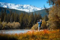 Amateur angler fishing on the rapid river. With mountains on the background. Altai, Russia stock images