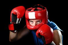 Amateur boxer man fighting with red boxing gloves and headgear protection. Amateur boxer man training shadow boxing with red fighting gloves and headgear royalty free stock photo