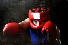 Amateur boxer man fighting with red boxing gloves and headgear protection. Amateur boxer man training shadow boxing with red fighting gloves and headgear royalty free stock photography