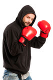 Amateur boxer wearing a hoodie and gloves. Amateur boxer wearing a black hoodie and red gloves on white background royalty free stock photos