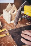 Amateur carpenter making a birdhouse. With a hammer royalty free stock photo