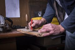 Amateur carpenter marking a line. With a protractor on plank royalty free stock image