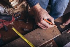 Amateur carpenter measures the board. Amateur carpenter marking a line with a protractor on plank stock image