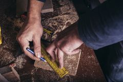 Amateur carpenter marking a line with a ruler. On board stock photos