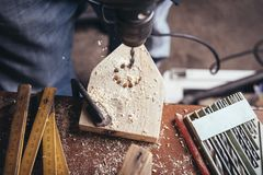 Amateur carpenter uses drill. On plank stock photography