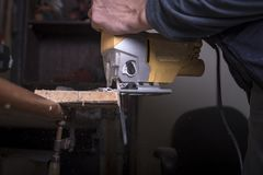 Amateur carpenter uses the jigsaw tool. To cat the board royalty free stock images