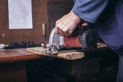 Amateur carpenter uses the power saw. To cat a board stock image