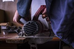 Amateur carpenter uses the power saw. To cat a board stock photography
