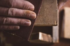 Amateur carpenter uses sanded paper. On wood royalty free stock photo
