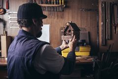 Amateur carpenter with wooden birdhouse. In a workshop stock photography