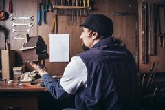 Amateur carpenter with wooden birdhouse. In a workshop stock image