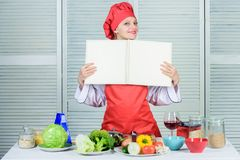 Amateur cook read book recipes. Girl learn recipe. Book by famous chef. Improve cooking skill. Book recipes. According. To recipe. Helpful culinary book. Woman stock image