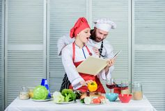 Amateur cook read book recipes. Improve cooking skill. Book recipes. Helpful culinary book. Woman chef and man cooking. Amateur cook read book recipes. Improve stock photo