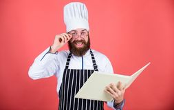Amateur cook read book recipes. Man learn recipe. Try something new. Cookery on my mind. Improve cooking skill. Book. Recipes. According to recipe. Man bearded stock photography