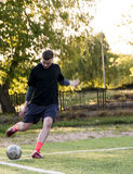 Amateur corner kick. Young amateur football player executing the corner kick stock image
