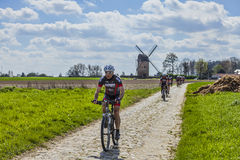 Amateur Cyclists on a Cobblestone Road. Templeuve,France- April 5, 2014:A group of  amateur cyclists riding their bicycles on the cobblestone road near the Stock Image