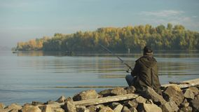Amateur fisherman fishing on river bank, recreational activity, rural getaway. Stock footage stock footage