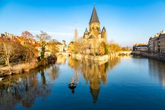 Amateur fisherman in an inflatable boat in center of Ville de Metz on Moselle river. Temple neuf - New Protestant church. Metz, France - Jan 20 2019: Two stock photography