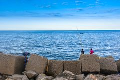 Amateur fishermen who fish from the dock. In a port stock photos