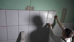Amateur man apply glue on tile and install it to wall. New apartment installation works. Handheld follow shot stock video