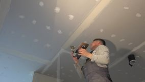 Amateur man apply joint compound between drywall panels. Static shot stock footage