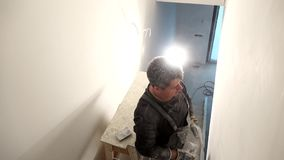 Amateur man grinds wall. Handyman aligns walls with sandpaper. Handheld. Amateur man grinds wall under lamp. Handyman aligns walls with sandpaper. Handheld stock video