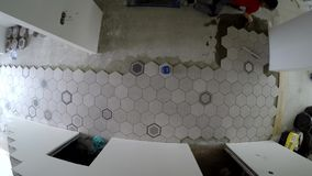 Amateur man laying hexagon shape tiles on corridor floor. Static timelapse. Top shot stock video footage