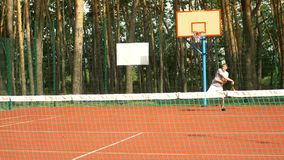 Amateur man playing tennis on outdoor court. Attractive active sporty man playing tennis on hardcourt during training session. Amateur tennis player hitting stock footage
