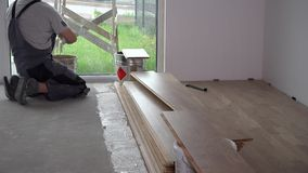 Amateur man put adhesive glue on mason floor. Preparation works for floor board laying. Static shot stock footage