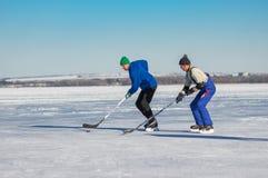 Amateur men playing hockey on a frozen river Dnepr in Ukraine. Dnepr, Ukraine - January 22, 2017: Amateur men playing hockey on a frozen river Dnepr in Ukraine stock photo