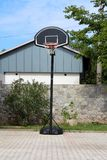 Amateur metal and plastic basketball hoop mounted on stone tiles backyard in front of stone wall surrounded with trees and cloudy. Amateur metal and plastic royalty free stock photography