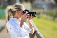 Amateur middle aged photographer. Taking pictures outdoors Royalty Free Stock Photo