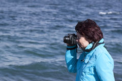 Amateur photographer. Woman amateur photographer shooting with marine background royalty free stock images