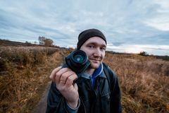 Amateur photographer admires the autumn scenery of the forest road. Landscape therapy concept. Close up portrait of amateur photographer admires the autumn royalty free stock photography