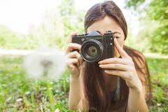 Amateur Photographer Nature. Young woman making picture of dandelion with vintage camera, female amateur photographer taking photo in nature stock images