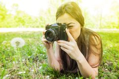 Amateur Photographer Nature. Young woman making picture of dandelion with vintage camera, female amateur photographer taking photo in nature stock photo