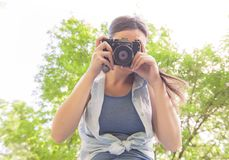 Amateur Photographer Outdoor. Young woman amateur photographer with vintage camera taking photo in nature stock images