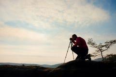 Amateur photographer takes photos with mirror camera on peak of rock. Dreamy fogy landscape, spring orange pink misty sunrise Royalty Free Stock Image