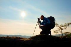 Amateur photographer takes photos with mirror camera on peak of rock. Dreamy fogy landscape, spring orange pink misty sunrise Royalty Free Stock Photos