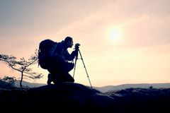 Amateur photographer takes photos with mirror camera on peak of rock. Dreamy fogy landscape, spring orange pink misty sunrise Royalty Free Stock Images