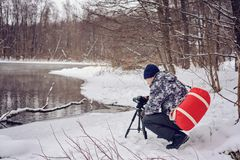 Amateur photographer takes a winter landscape on the lake in the forest. copy space.  royalty free stock images