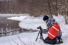 Amateur photographer takes a winter landscape on the lake in the forest. copy space.  stock image