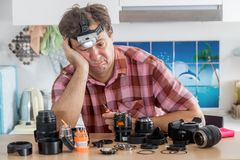 Amateur photographer is trying to repair his camera. Stock Photos