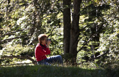 Amateur photographer. Woman amateur photographer shooting in the forest stock photography