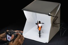 Amateur photographer working on mirrorless camera to shooting motrocycle model in mini lightbox.  stock image