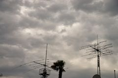 Amateur radio antennas above the roofs of houses. Two large antennas photographed on a very cloudy day stock photos