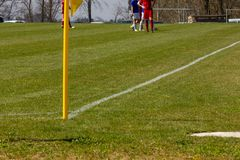 Amateur soccer field. With green lawn and white lines with yellow pole on the corner edge royalty free stock photography